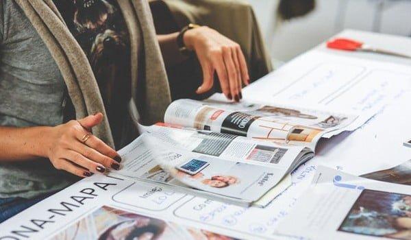 a women fliping through a freshly published magazine