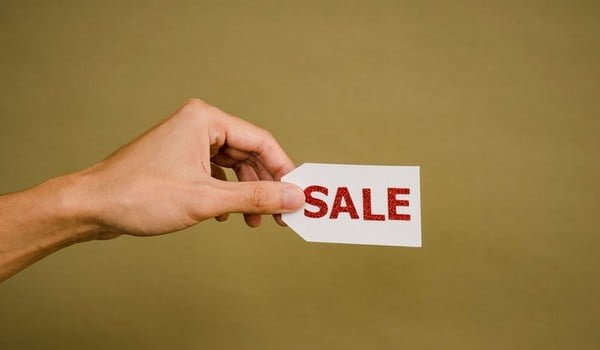 A persons hand with a sale tag